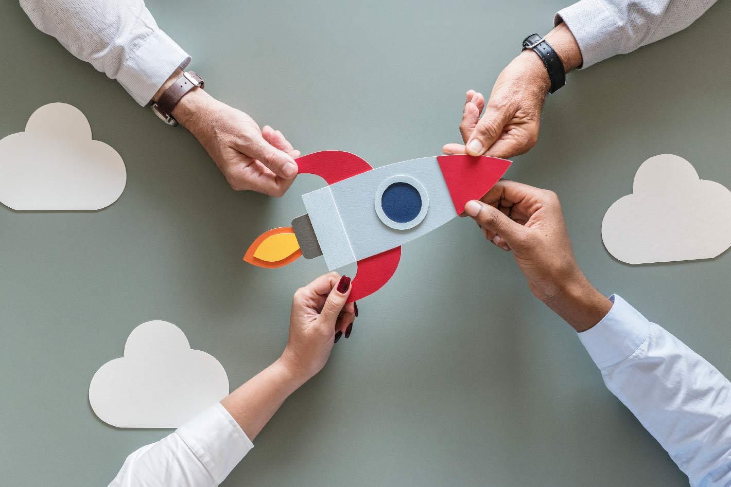 Startupbild Rakete gehalten von 4 Händen